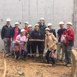 University of MD students pose for a photo with rocks that they excavated