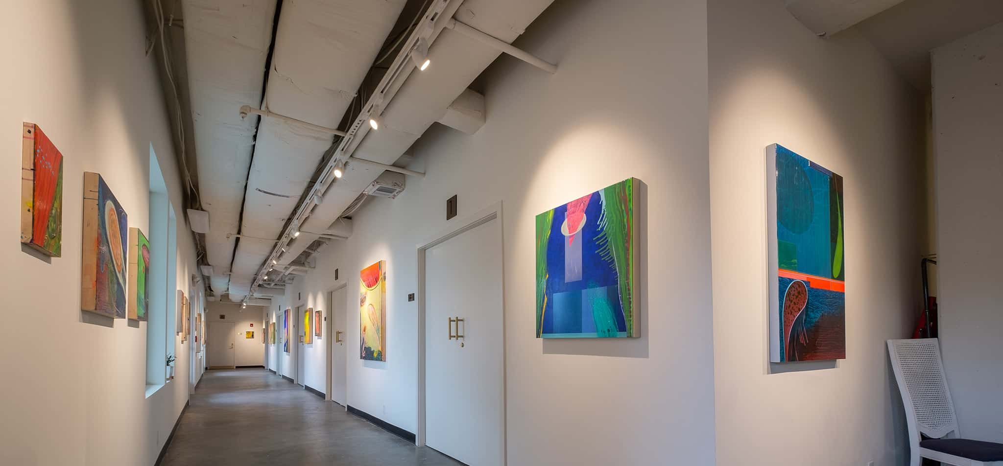 Hallway filled with paintings at Portico Gallery and Studios